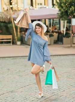 Szczęśliwa młoda kobieta w kapeluszu i sukni trzyma torby na zakupy w jej rękach i uśmiecha się w letnim mieście