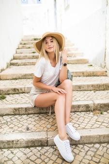 Szczęśliwa młoda kobieta w kapeluszu lato siedzi na schodach na ulicy miasta