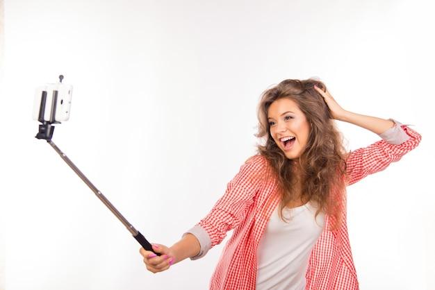 Szczęśliwa młoda kobieta w kapeluszu robi selfie zdjęcie z kijem