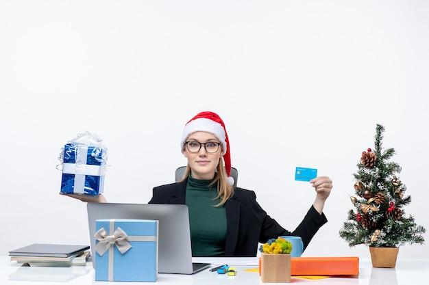 Szczęśliwa młoda kobieta w kapeluszu świętego mikołaja i nosząc okulary siedzi przy stole przedstawiającym prezent świąteczny i kartę bankową na białym tle
