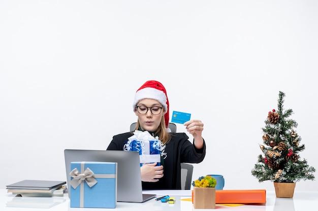 Szczęśliwa młoda kobieta w kapeluszu świętego mikołaja i nosząc okulary siedzi przy stole trzymając prezent na boże narodzenie i kartę bankową na białym tle nagrania