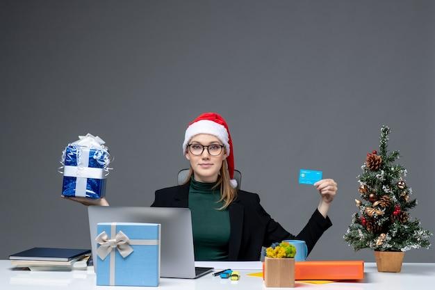 Szczęśliwa młoda kobieta w kapeluszu świętego mikołaja i nosząc okulary siedzi przy stole trzymając prezent na boże narodzenie i kartę bankową na ciemnym tle