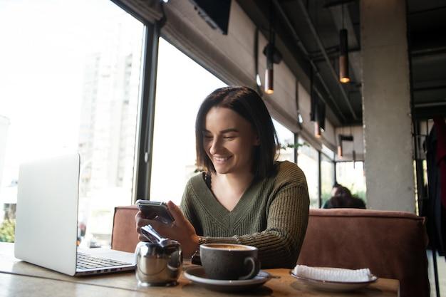 Szczęśliwa młoda kobieta w kawiarni uśmiecha się, patrząc na smartfona.