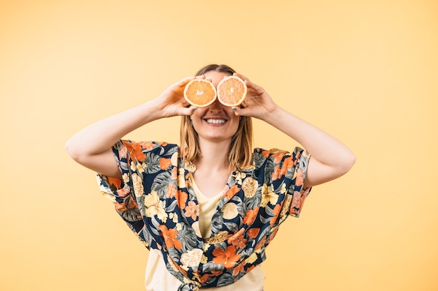 Szczęśliwa młoda kobieta w kwiecistej koszuli trzymająca pomarańczowe połówki zakrywające jej oczy