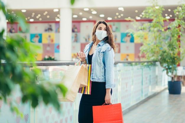 Szczęśliwa młoda kobieta w masce medycznej spaceru w centrum handlowym z dużą ilością toreb na zakupy w rękach.