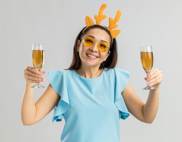 Szczęśliwa młoda kobieta w niebieskiej górze, ubrana w zabawną obręcz z rogami jelenia i żółtymi okularami, trzymająca dwie szklanki szampana, uśmiechnięta wesoło
