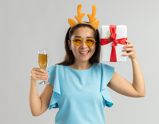 Szczęśliwa młoda kobieta w niebieskiej górze ubrana w zabawną obręcz z rogami jelenia i żółtymi okularami trzymająca kieliszek szampana i prezent gwiazdkowy uśmiechnięty wesoło