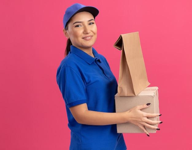Szczęśliwa młoda kobieta w niebieskim mundurze i czapce trzyma papierową paczkę i karton patrząc na przód uśmiechnięty pewny siebie stojący nad różową ścianą