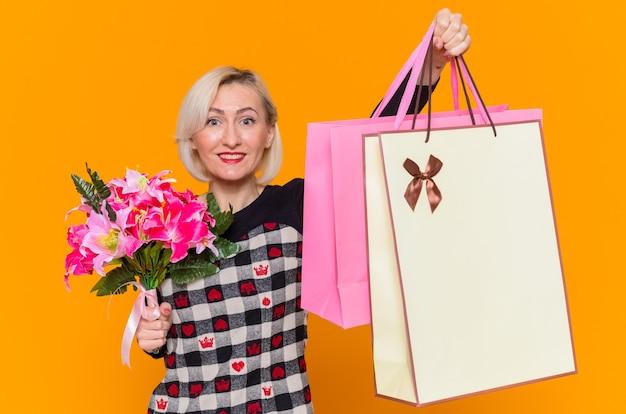 Szczęśliwa młoda kobieta w pięknej sukience trzymająca bukiet kwiatów i papierowe torby z prezentami, uśmiechnięta wesoło, świętująca międzynarodowy dzień kobiet stojąca nad pomarańczową ścianą