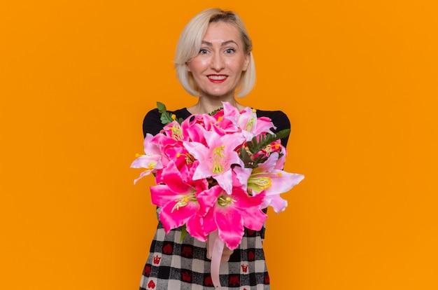 Szczęśliwa młoda kobieta w pięknej sukni z bukietem kwiatów