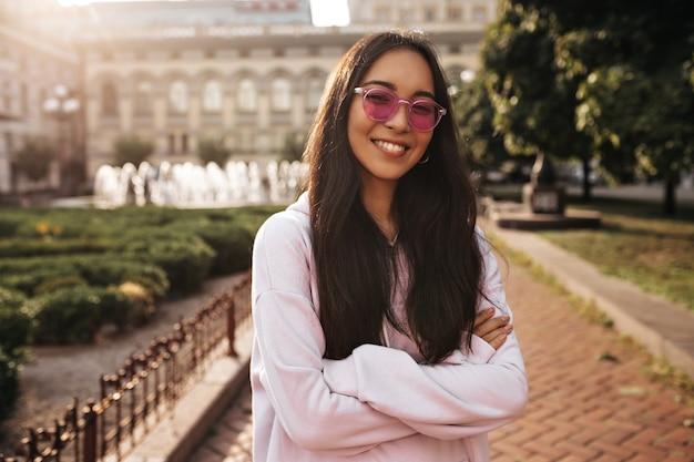 Szczęśliwa młoda kobieta w różowej bluzie z kapturem szczerze się uśmiecha