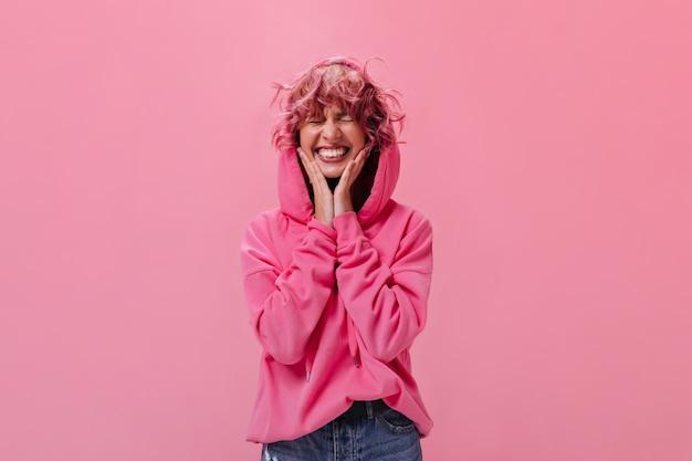 Szczęśliwa Młoda Kobieta W Różowej Bluzie Z Kapturem Szeroko Uśmiecha Się Na Białym Tle Darmowe Zdjęcia