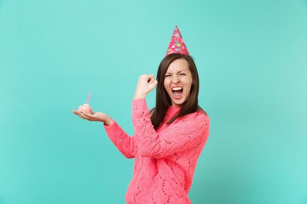 Szczęśliwa młoda kobieta w różowy sweter z dzianiny, kapelusz urodziny krzyczeć robi gest zwycięzcy, trzymając w ręku ciasto ze świecą na białym tle na tle niebieskiej ściany. koncepcja życia ludzi. makieta miejsca na kopię.