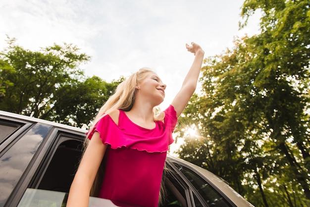 Szczęśliwa młoda kobieta w samochodowej ręce up