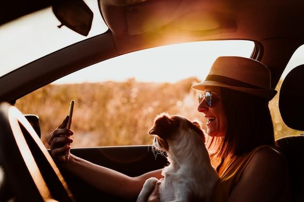 Szczęśliwa młoda kobieta w samochodzie z psem o zachodzie słońca