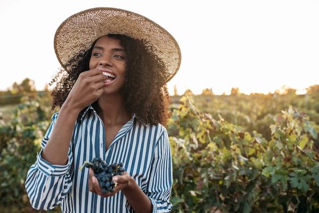 Szczęśliwa młoda kobieta w słomianym kapeluszu łasowania winogronach w winnicy