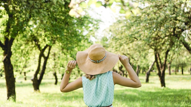 Szczęśliwa młoda kobieta w słomkowym kapeluszu w słonecznym ogrodzie