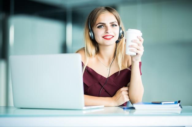 Szczęśliwa młoda kobieta w słuchawkach w call center i picia kawy w biurze.