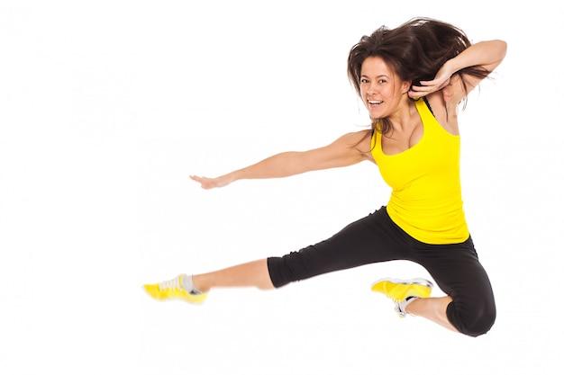 Szczęśliwa młoda kobieta w sprawności fizycznej odzieży skacze