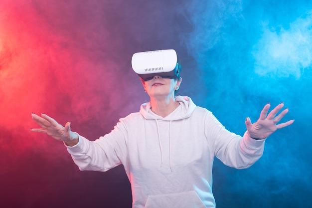 Szczęśliwa młoda kobieta w średnim wieku za pomocą zestawu słuchawkowego wirtualnej rzeczywistości na czerwono-niebieskiej ścianie.