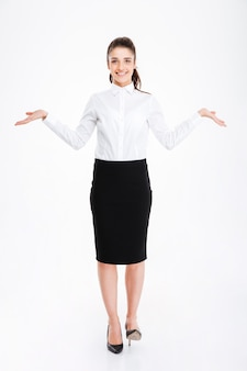 Szczęśliwa młoda kobieta w stroju formalnym trzymająca miejsce na kopię w obu rękach, stojąc na białym tle