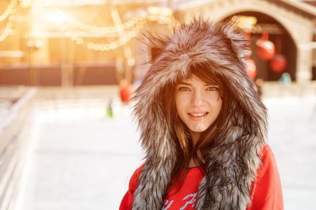 Szczęśliwa młoda kobieta w wilczym kapeluszu w zimie przy lodowiskiem pozuje w czerwonym pulowerze na zewnątrz po południu