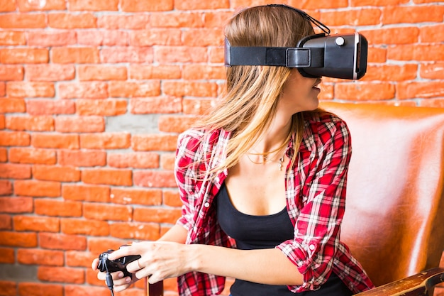Szczęśliwa młoda kobieta w zestawie słuchawkowym wirtualnej rzeczywistości lub okularach 3d i słuchawkach grających w gry wideo z kontrolerem gamepad w domu