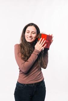 Szczęśliwa młoda kobieta właśnie otrzymała pudełko upominkowe na urodziny