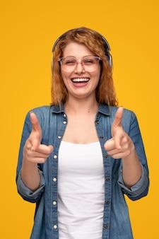 Szczęśliwa młoda kobieta wskazuje na aparat w słuchawkach