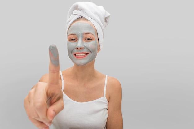 Szczęśliwa młoda kobieta wskazuje na kamerze z palcem błoto maska. ona się uśmiecha. młoda kobieta nosi biały t-shirt na ciele i ręcznik wokół włosów. na szarym tle.