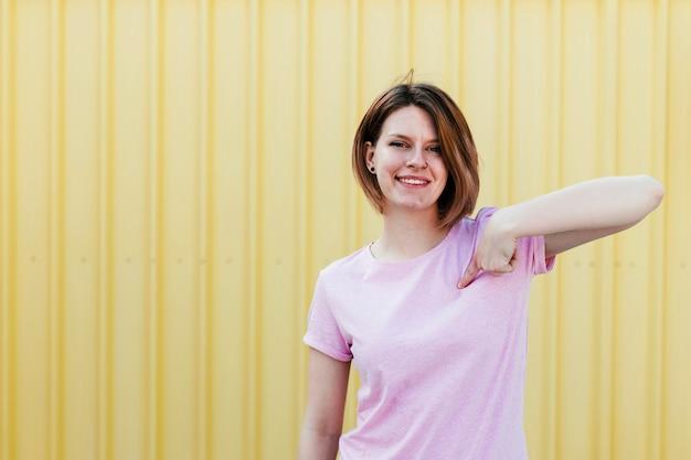 Szczęśliwa młoda kobieta wskazuje palec w kierunku ona