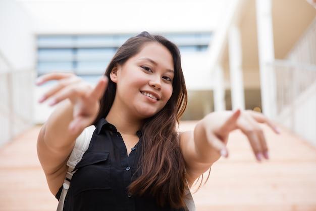 Szczęśliwa młoda kobieta wskazuje przy kamerą z plecakiem