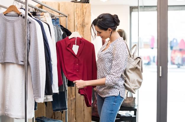 Szczęśliwa młoda kobieta wybiera czerwoną bluzkę ze sklepu