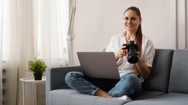 Szczęśliwa młoda kobieta z aparatem fotograficznym za pomocą laptopa w domu. fotograf trzyma aparat i uśmiecha się.