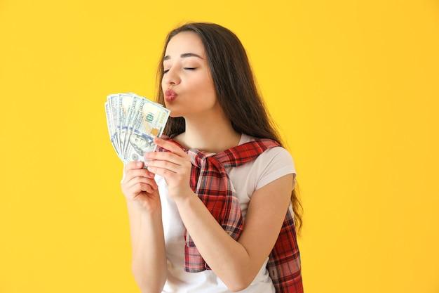 Szczęśliwa młoda kobieta z banknotami dolara na kolorowym tle