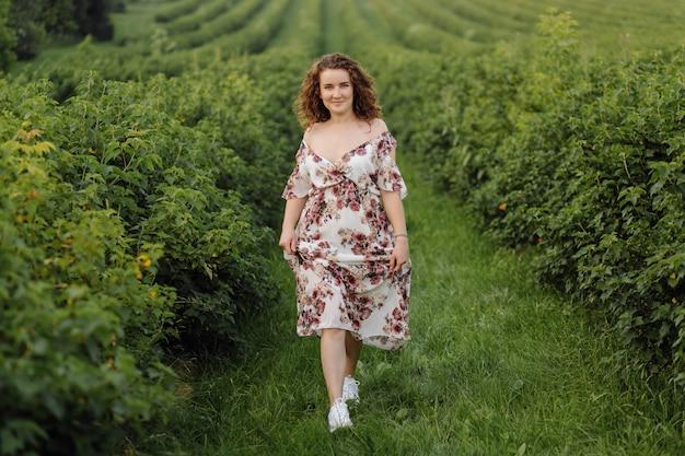 Szczęśliwa młoda kobieta z brązowymi kręconymi włosami, ubrana w sukienkę, pozowanie na zewnątrz w ogrodzie