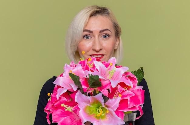 Szczęśliwa młoda kobieta z bukietem kwiatów