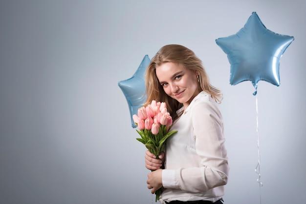 Szczęśliwa młoda kobieta z bukietem tulipany