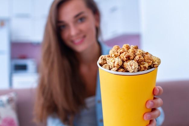 Szczęśliwa młoda kobieta z chrupiącym karmelu popkornu pudełkiem podczas oglądanie filmu w domu