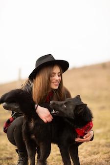 Szczęśliwa młoda kobieta z czarnym kapeluszem
