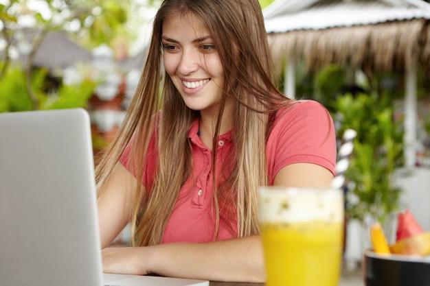 Szczęśliwa młoda kobieta z długimi luźnymi włosami siedzi przed laptopem, korzystając z bezpłatnego bezprzewodowego połączenia z internetem, patrząc na ekran z radosnym uśmiechem, czytając wiadomości od przyjaciół online