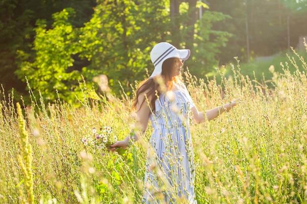 Szczęśliwa młoda kobieta z długimi włosami w kapeluszu i sukience ciągnie ręce w kierunku roślin podczas chodzenia