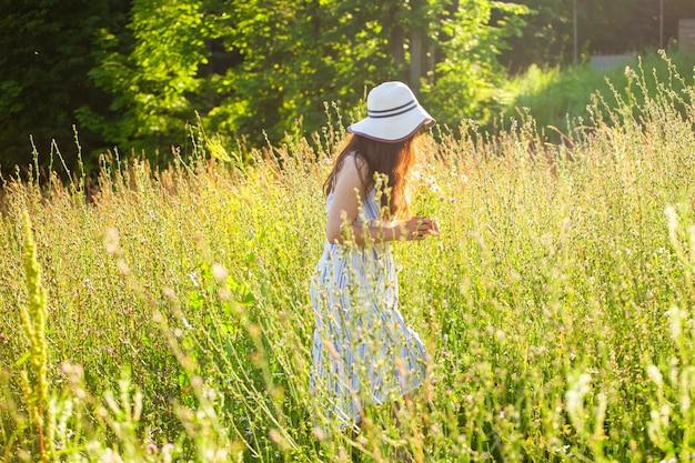 Szczęśliwa młoda kobieta z długimi włosami w kapeluszu i sukience ciągnie ręce w kierunku roślin