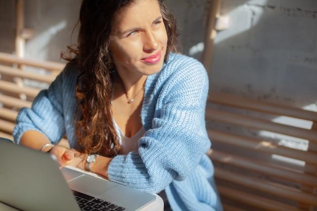 Szczęśliwa młoda kobieta z długimi włosami w niebieski ciepły sweter z dzianiny siedzi w pobliżu okna i pracuje na komputerze zdalnie w domu. wnętrze domu z widokiem na okno. elegancki bizneswoman z uśmiechem.