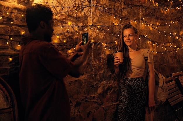 Szczęśliwa młoda kobieta z drinkiem pozuje do swojego afrykańskiego chłopaka ze smartfonem