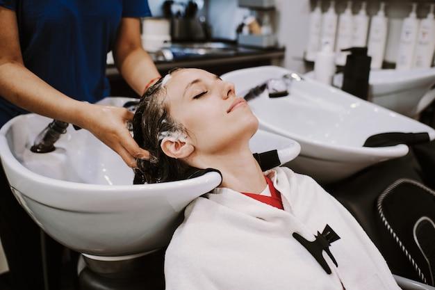 Szczęśliwa młoda kobieta z fryzjerem mycia głowy w salonie fryzjerskim