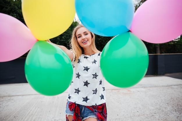 Szczęśliwa młoda kobieta z kolorowymi lateksowymi balonami na zewnątrz