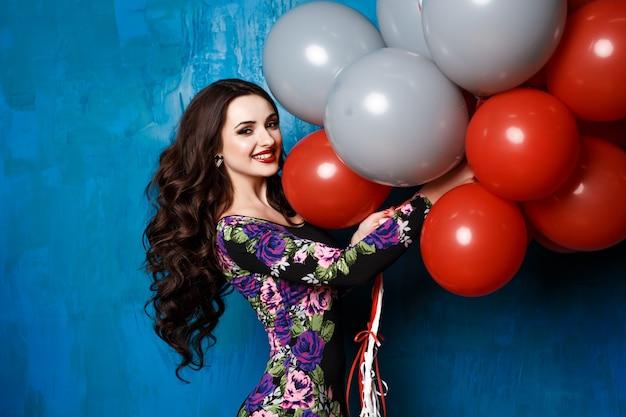 Szczęśliwa młoda kobieta z kolorowymi lateksowymi balonami. uroda, ludzie, styl, wakacje i koncepcja mody - szczęśliwa młoda kobieta lub nastolatka w sukience z balonów z helem