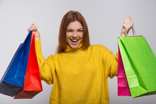 Szczęśliwa młoda kobieta z kolorowymi torba na zakupy