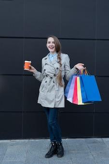 Szczęśliwa młoda kobieta z kolorowymi torbami i papierową filiżanką. czarna ściana ulicy